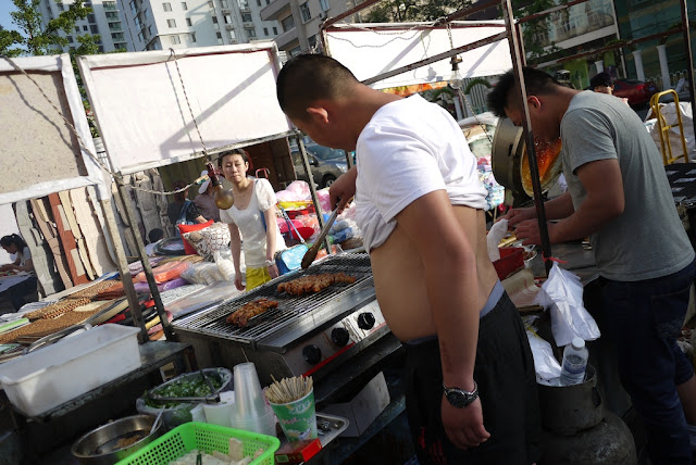 man with shirt lifted over his stomach grilling meat
