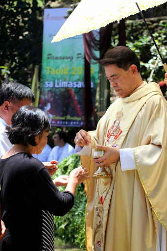 Priest in Limasawa gives the Holy Communion