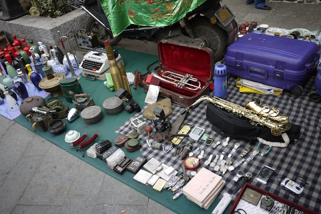 saxophone, trumpet, watches, and other items for sale outside Tianxinge Antique City in Changsha, China