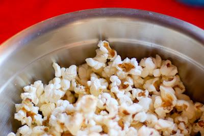 Silver bowl full of plain popcorn.