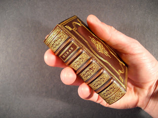 A photograph of a hand holding a small leather book with gold stamping.