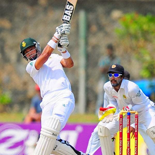 South African cricketer Alviro Petersen (L) is watched by Sri Lankan wicketkeeper Dinesh Chandimal (R) as he plays a shot during the first day of the opening Test match between Sri Lanka and South Africa at the Galle International Cricket Stadium in Galle on July 16, 2014.