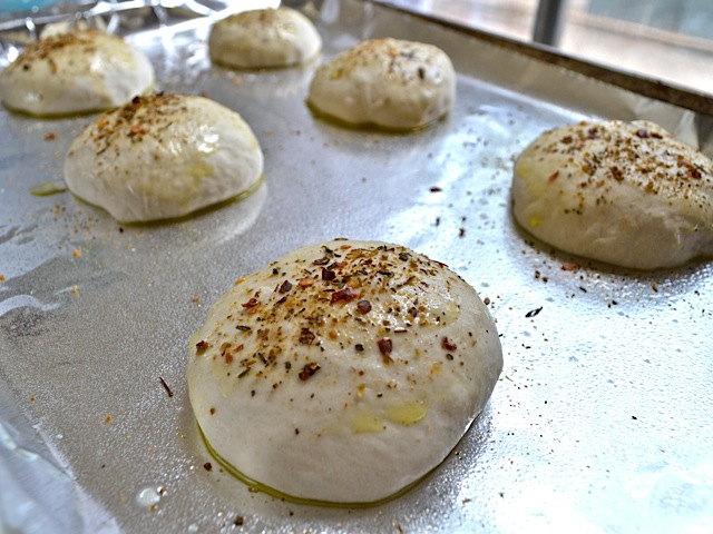 Add seasoning to the top of unbaked focaccia rolls