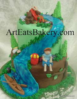 Boy's two tier camping creative birthday cake design with edible tent, bear, moose, campfire, trees, canoe, backpack and boy