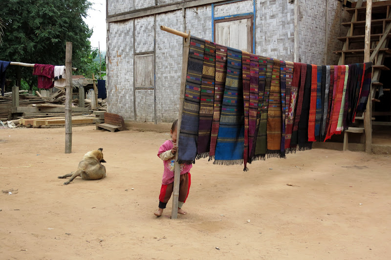 Shy little girl hiding behind weaving display