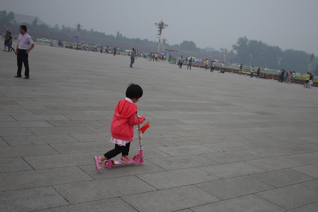 little girl riding a pink kick scooter at Tiananmen Square