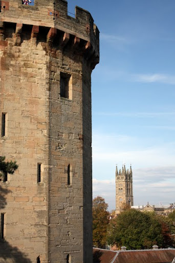 A tower at Warwick Castle in England with church in Warwick in the background