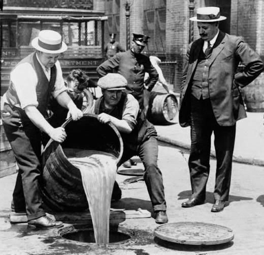 Barris de bebida alcoólica sendo despejados nos esgotos de Nova York, 1920.