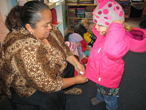 Teacher helping a child put on her jacket.