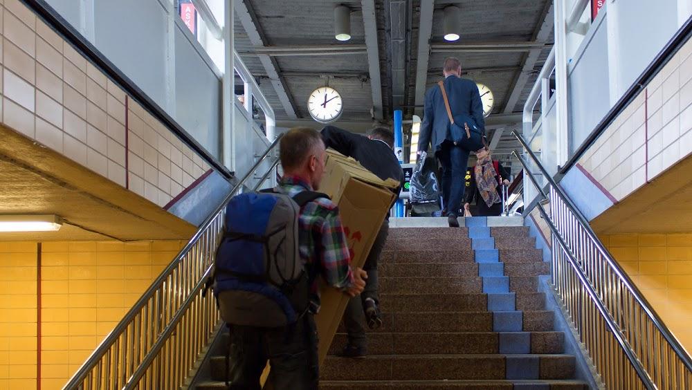 Med hjälp fick mannen upp kartongen för trappan till spåre 11 och 12