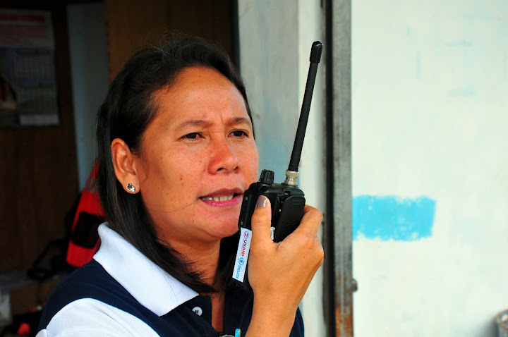 Photo of Lizpeth talking into a walkie-talkie.