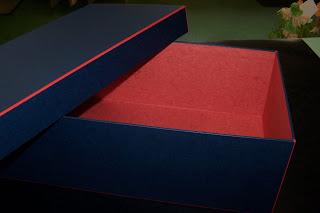 Gefügte Schachtel mit rotem Gewebefalz. Mit Linsonpapier überzogen und mit Elefantenhaut in rot ausgefüttert.