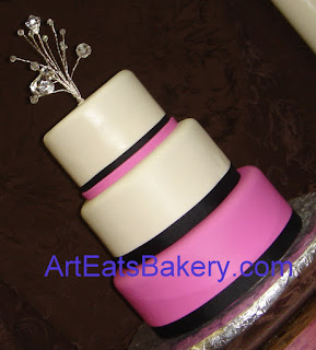 Three tier fondant wedding cake with black ribbons and crystal topper.
