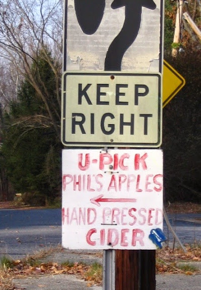 Hand-painted sign with and a left-pointing arrow that reads: U-Pick, Philss Apples, Hand-Pressed Cider