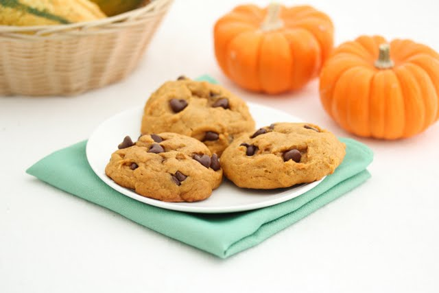 photo of three cookies on a white plate with pumpkins in the background