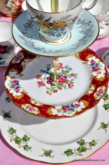 colourful mismatched three-tiered vintage cake stand with teacup top