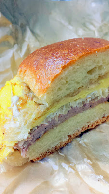 Portland Penny Diner's breakfast sandwich of PDXWT duck bologna, sauerkraut, coffee mayo, egg, american cheese, on the soft, buttery, and fresh parker house roll.
