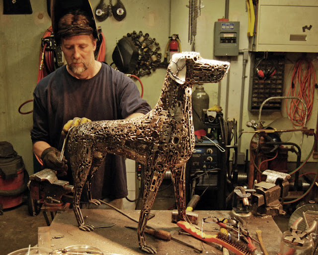 Brian Mock metal köpek heykeli üzerinde çalışıyor