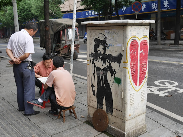 two men playing xiangqi next to an electric box with a drawing of a woman