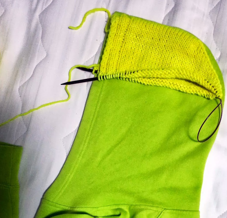 The top of a bright yellow knitted hood laid against the hood of a commercial hooded sweatshirt