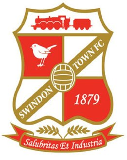 Swindon Town FC badge. A shield rimmed in gold with a red steam train at the top, a gold football in the centre with band running diagonally through it which reads Swindon Town FC there is a harlequin pattern on the rest of the shield with two red and two white squares. The top left square is red with a white robin in it. The bottom right has the date 1879. Beneath the badge is a scroll which reads Salubrita et Industria