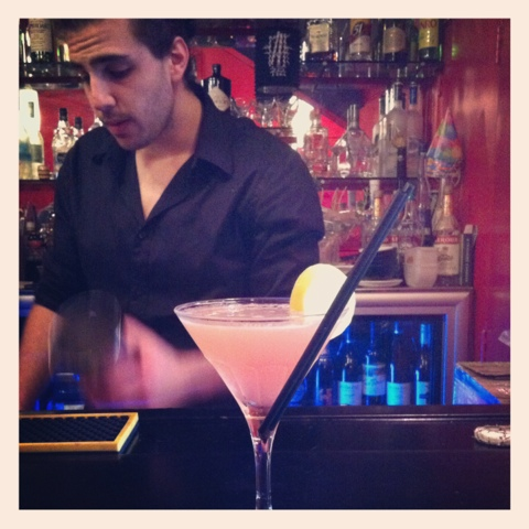 A picture of a cocktail in a martini glass, with a barkeep in the background.