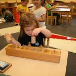 Montessori preschool girl in Irvine working with cylinder block in private school classroom.