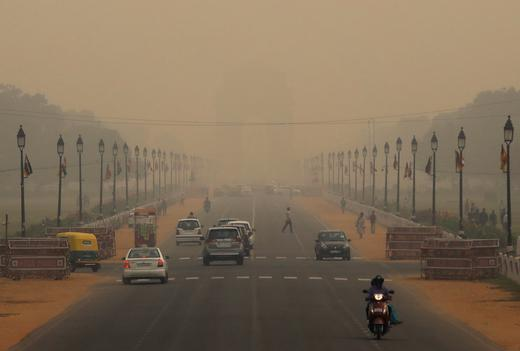Vehicles drive through smog near India Gate in...