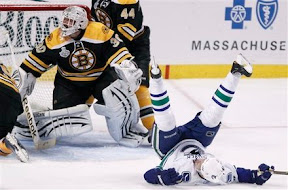 Henrik Sedin down on the ice after being hit by Tim Thomas