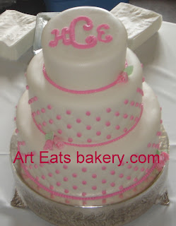 White Fondant Three Tier Wedding Cake With Pink Edible Pearls Monogram And Icing Flowers