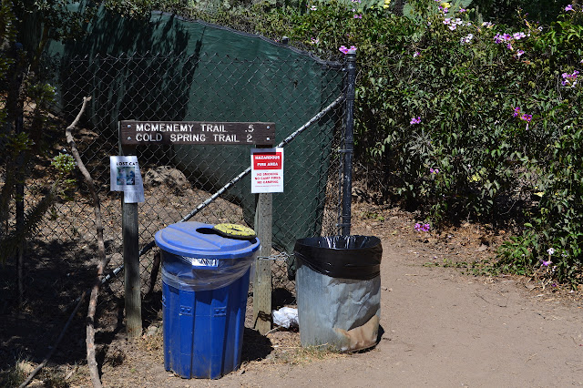 sign with mileages, garbage and recycling cans below, trail starting between two fences