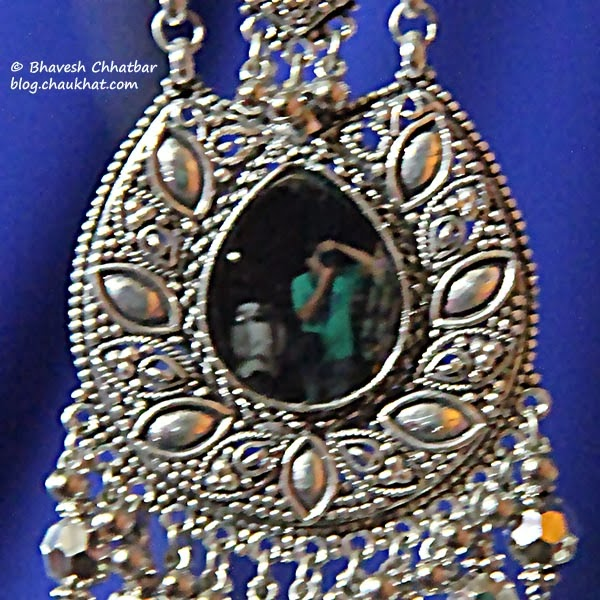 Photographer's reflection in the mirror of a rustic pendant