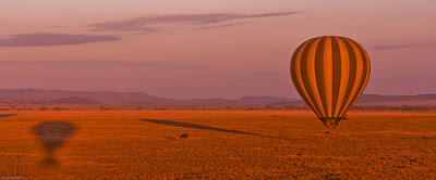 striped hot air balloon floating over the Serengeti
