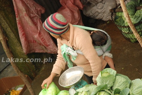 Mother carrying her child while selling vegetables in Mount Polis, Ifugao