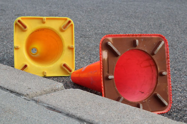 two caution cones, one orange and one yellow, lying in a gutter