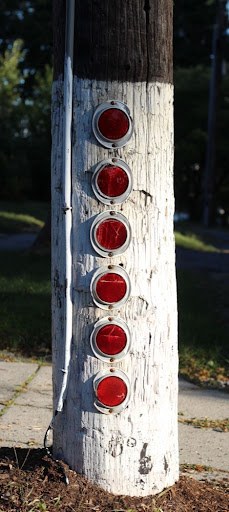 a column of six red reflectors on a white-painted utility pole