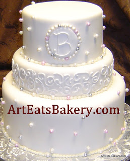 Three tier ivory fondant custom wedding cake with pink and silver sugar pearls, monogram and curlicue lace design