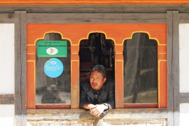 Bhutanese man looking out of his shop window near Kuje Lakhang, Bumthang