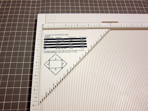 I inserted the envelope making triangle into the grooves of the scoring board, flush with the top and side measurement rails.