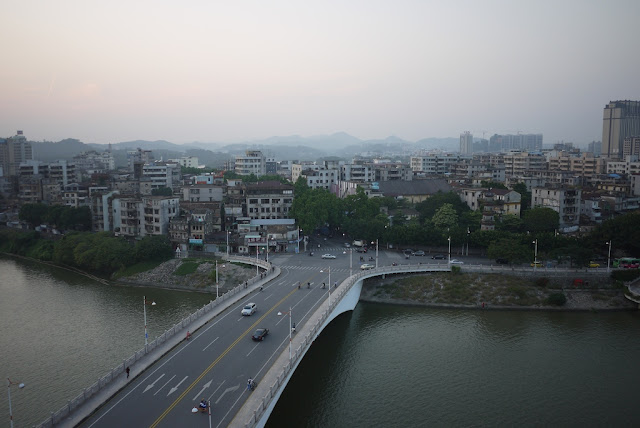 bridge over a river in Huizhou with buildings and mountains in the background