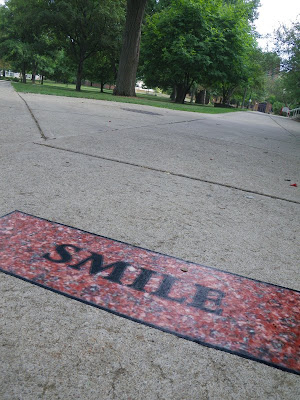 Smile sign on sidewalk