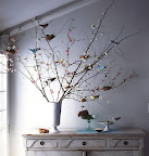 crepe paper birds perched among a large arrangement of flowering branches