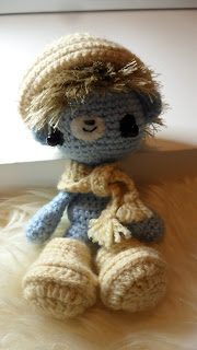 Little blue MJ Henry is the most adorable pale sky blue, his hair has been crocheted on separately so that it flows in the direction of real hair which is still on the round but slightly back on the head. This creates a tiny dip like a soft spot so looks very natural. The hair is in a complimentary colour to the body of the blue doll and is tan brown. The wool used for the hair has long mohair fibres, I used a very small hook to get as many fibres into the hair as possible. There are so many individual hair strands that you can actually brush and style it. I placed the bear on a deep pile cream sheepskin rug, he looks comfortable. The bear is 9 inches tall. His head makes up 3 inches, he has half circle sticky out ears, his eyes are big black beads sat on a circle of black felt. When light shines on the beads it makes it look like he has glowing eyes. He has a little black note which is just a few stitches in a 5mm rectangle and a little crooked mouth which gives him a cheeky grin, these are on a little oval of white felt set slightly above the eyes. Setting the nose slightly above the eyes is what gives him the cute traditional amigurumi look. He wears a scarf, hat and has big boots which are in a lighter tan. When you take his boots off he has proper little shaped feet with toes. The toes are my favourite bit of him and are mega cute.