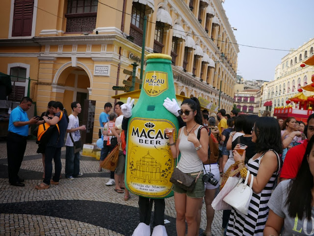 young woman in sunglass posing next to the Macau Beer mascot