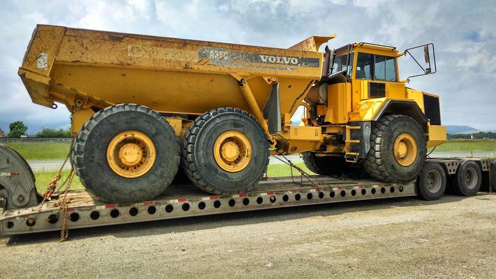huge volvo rock dump truck loaded on flatbed trailer