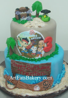 Two tier boy's custom creative Jake the Pirate fondant birthday cake design idea with edible parrot, palm trees, treasure chest and sword