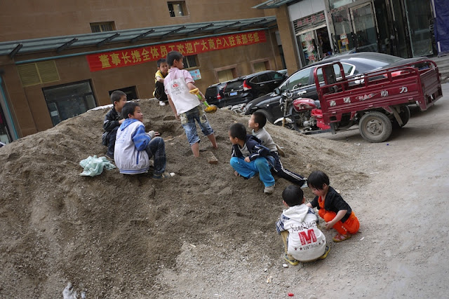 kids playing on a pile of dirt in Xining, Qinghai, China