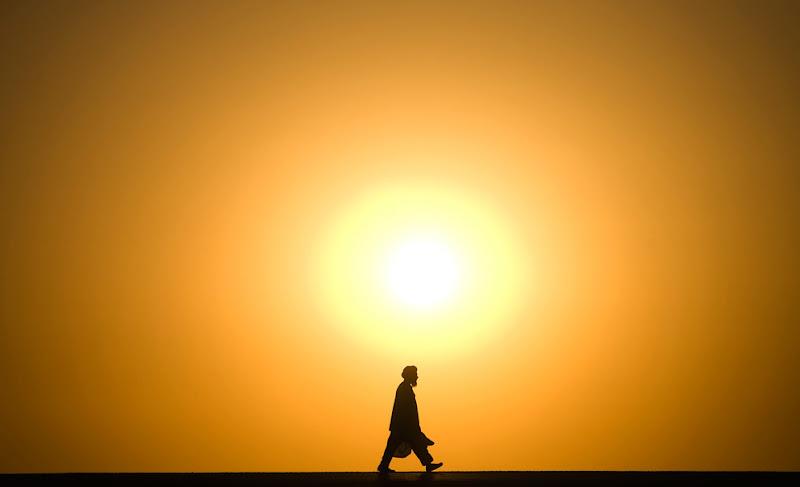 Um homem afegão caminha na rua enquanto o sol se põe sobre o distrito Delaram, na província de Nimroz, no sul do Afeganistão em 20 de janeiro de 2010. (REUTERS / Marko Djurica)