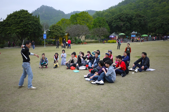 group watching man with nunchaku at Bailian Dong park in Zhuhai China