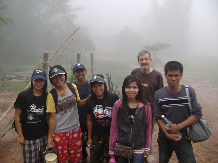 Portrait of seven members of the GMFT family against a foggy, outdoor background